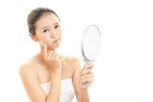 手鏡を覗き込みながら悩んでいる女性