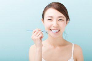 笑顔で歯を磨く女性