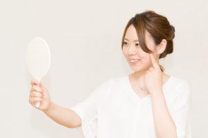 手鏡を使い自分の歯を見ている女性