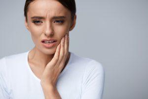 歯が痛そうに頬をおさえている女性