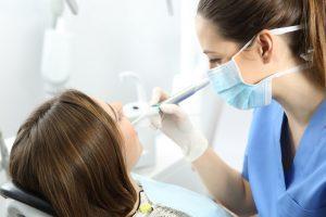 歯の治療を受ける女性と歯の治療をする女性歯科医師