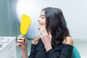 鏡で歯をチェックしている女性