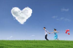 ハートの雲が浮かんでいる草原を男性と女性が風船をもって手をつないで走っている