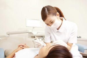 真剣な表情で歯の治療を行う女性歯科医