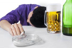 酒とたばこに溺れる男性