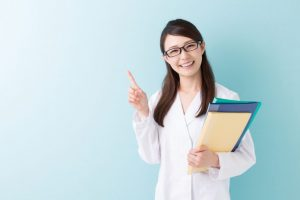 笑顔で案内をする眼鏡をした女性看護師