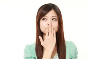 口臭が気になるため口元を手でおさえている女性