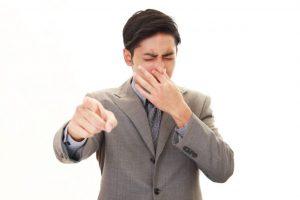 男性が口を押えて顔をしかめている