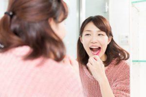 鏡の前で笑顔で歯を磨いている女性
