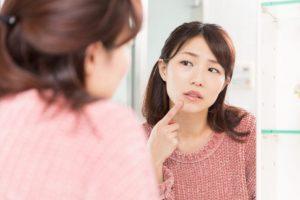 肌荒れしていないか心配で自分の顔を鏡でチェックする女性