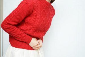 腹痛に悩む赤いセーターを着た女性