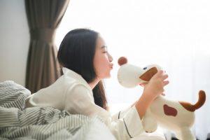犬のぬいぐるみにおはようのキスをしようとしている女性