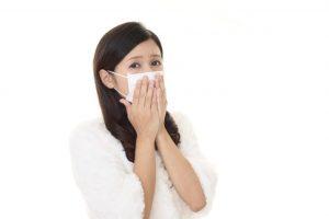 マスクをした女性が口を押えている