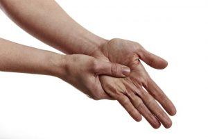 手のツボを押している女性