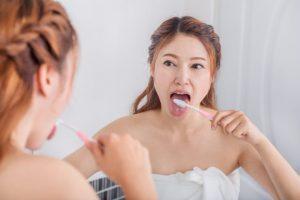口臭対策のために舌を磨く女性