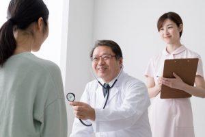 聴診器を当てようとしている男性医師
