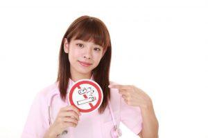 禁煙のマークを持っている女性歯科医