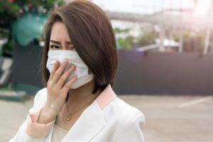 嫌そうに口元のマスクを手で押さえる女性
