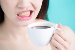 女性がコーヒーカップを片手に歯をむき出しにしている