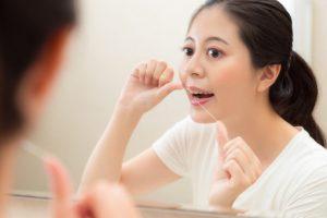 フロスを使って歯間を掃除している女性