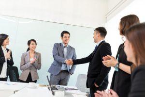 男性が握手を交わしていてまわりで拍手をしている人がいる