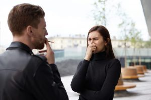タバコを吸う男性に対して最悪といった顔をする女性