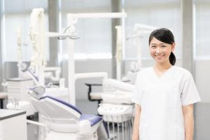 ユニットの前に立っている笑顔の女性歯科衛生士