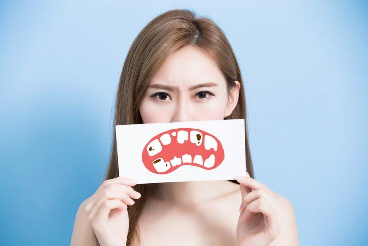 眉をひそめた女性が虫歯のある口のイラストを持っている
