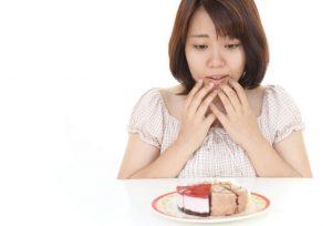 ケーキ食べたいでも今ダイエット中だし…食べても運動すればいいよねと悩んでいる女性