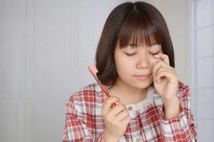 女性が歯ブラシをもって泣いている