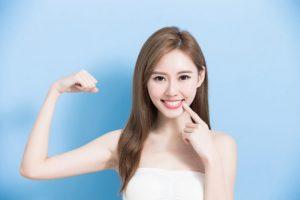女性が歯を刺しながら右腕で力こぶをつくっている