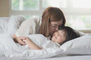 息子の頬に目覚めのキスをする母親