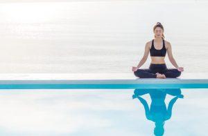 プールサイドで瞑想している女性