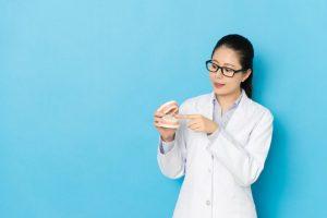 眼鏡で白衣を着た女性が歯の模型をもって指さしている