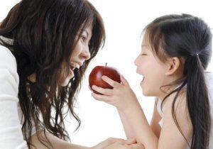 母親にリンゴを食べさせてあげる少女