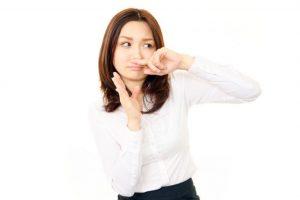 手で鼻を覆う女性
