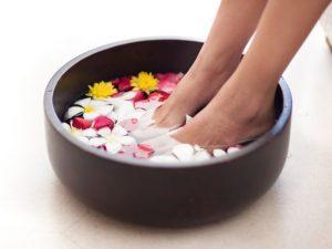 花が入った水に足をつける女性