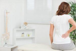 ベットに座りながら右手で腰をおさえる白い服を着た茶髪の女性
