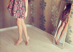 花柄のスカートをはいた女性が鏡の前で後ろ向きにポーズをとっている