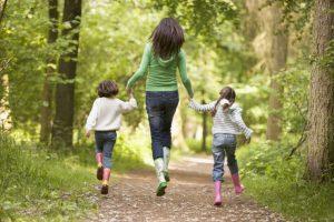 林間をスキップをしている母親と子供2人