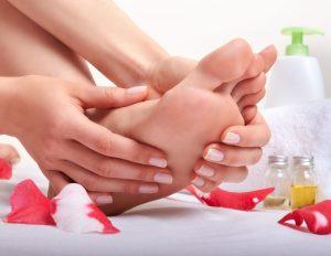 マッサージオイルを使って足のマッサージをしている女性