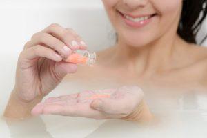 お風呂でピンクの粉を瓶から出し手に乗せている女性