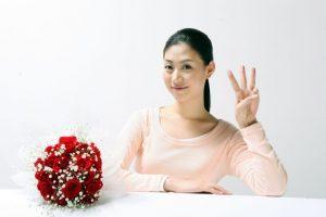 3本の指を出している女性