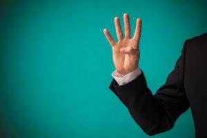 指で4を作っている男性