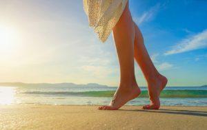 砂浜で踵立ちをしている女性