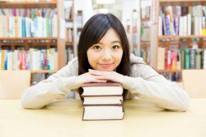 本の上に手を起きその上に顎を乗せている女性