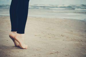 砂浜で爪先立ちをしている女性