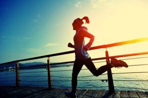 美しい朝日の中をランニングする女性