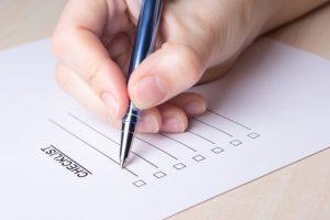 ペンを持ってチェックリストに書こうとしている手