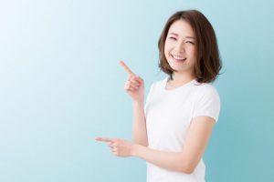 両手の人差し指を指している女性